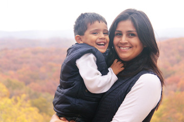 Smiling mother holding son outdoors in the fall