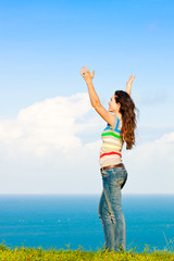 Beautiful young woman with her arms in the air