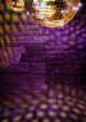 Golden mirror balls reflect lights on purple disco brick wall
