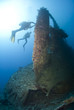 Scuba divers exploring the propellor area of a shipwreck.