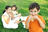 Small group of children in nature eating together, sandwiches poster