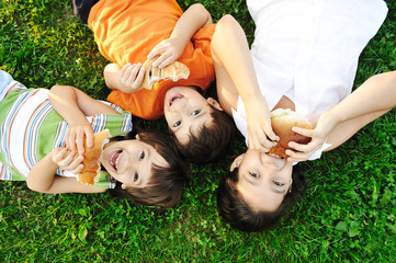 Three children laying on grass on ground, eating