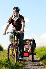 Familie fährt Fahrrad im Sommer mit Anhänger