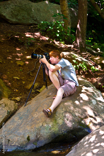 boy takes pictures at natural Waterfall in national park