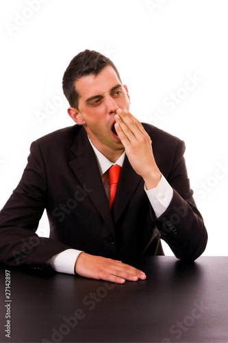yawning young business man on the desk, isolated on white backgr