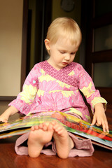 2 years old girl reading or browse through pop-up book