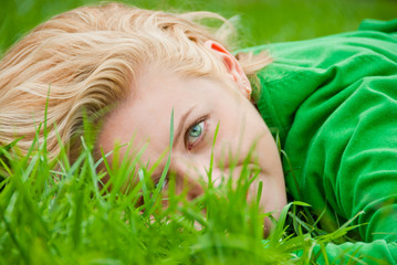 young blonde lying in a grass