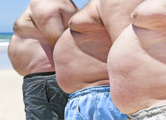 Close up of three obesely fat men on the beach