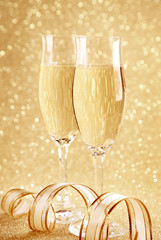Two glasses of champagne and golden decoration