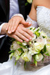 Hands of a newly-married couple with rings on a bouquet