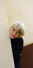 enfant  blond secachant derrière un mur