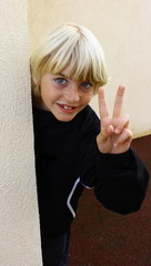 enfant blond faisant un signe de la main