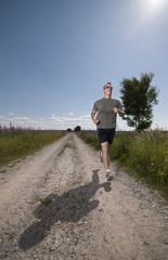 Athletic male running on field road on hot summer day.