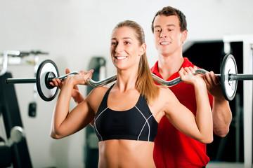 Personal Trainer und Frau im Fitnessstudio
