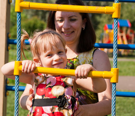 Girl climbs on the ladder of child, mother supports her