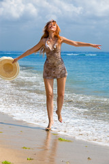 Young graceful woman goes on coast of ocean with straw hat