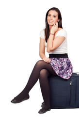 Pretty girl sitting on a suitcase