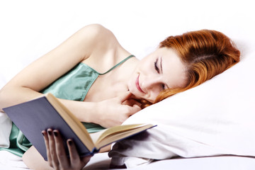 Lying girl in the bed reading book