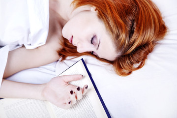 White nightie lying girl in the bed near book
