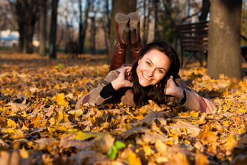 Beautiful young woman lying in autumn leaves