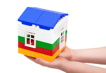 house of blocks in children's hands isolated on white