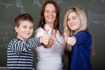 lehrerin und schüler zeigen daumen hoch