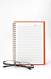 orange notebook and eyeglasses