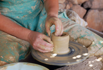 close up of the hands of a potter creating a jug on the circle