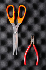 red pliers and orange scissors on sponge