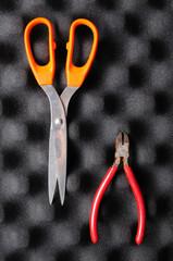 red pliers and orange scissors on sponge