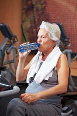 Seniorin im Fitnesscenter trinkt Wasser