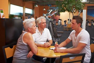 Fitnesstrainer berät zwei Senioren