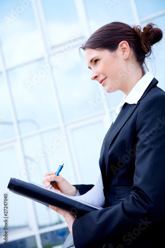 Young business woman outside, writing a memo