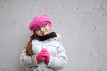 Adorable small girl in bright pink hat