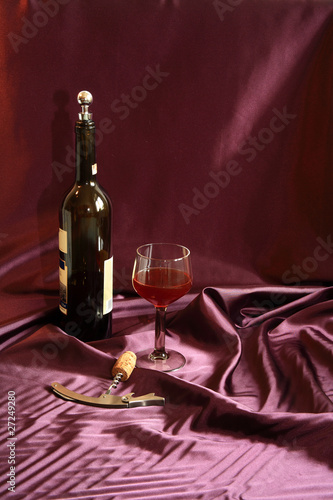 bottle of red wine, glass and corkscrew