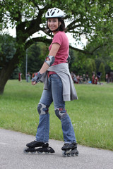 Young woman learning to ride on rollerblades in the park.