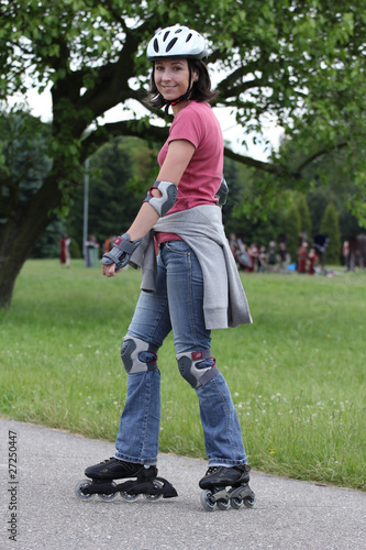 Leinwandbild Motiv Young woman learning to ride on rollerblades in the park.