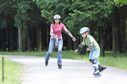 Happy family learning to ride on rollerblades