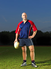 Rugby Player with his rugby ball looking proud