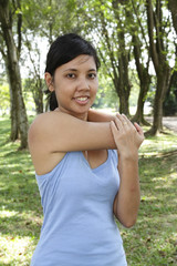 An Asian woman performing some stretching exercise