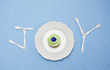 "teaspoons and plate with cupcake spelling ""joy"" on tablecloth"