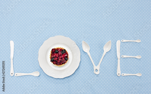 "silverware and plate with tart spelling ""love"" on tablecloth"