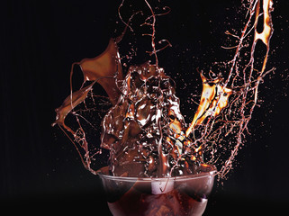 close up of chocolate syrup splashing from glass