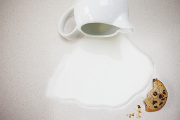 spilled milk from pitcher and cookie crumbs