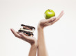 woman cupping green apple above chocolate bars