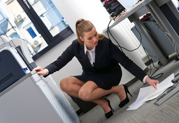 secretary lifting papers from the floor