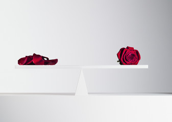red rose and rose petals balanced on opposite ends of seesaw