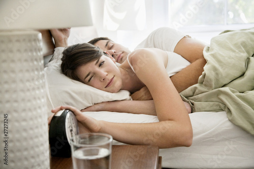 couple in bed waking to alarm clock