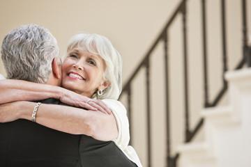 smiling senior couple hugging