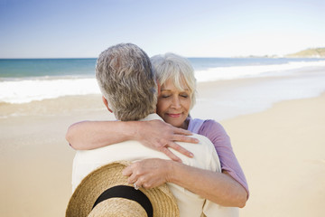 smiling senior couple hugging on beach
